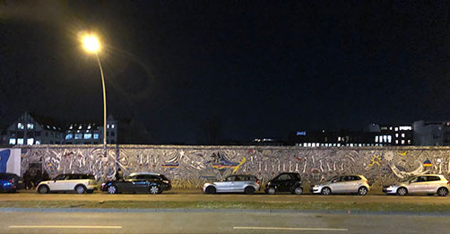 ein Stück bunte Mauer am Spreeufer in Berlin, an der East-Side, bei Nacht, mit viel Verkehr